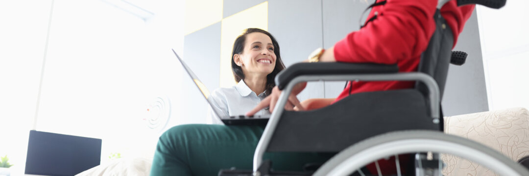 Disabled woman in wheelchair communicates with smiling friend with laptop on her lap. Psychological assistance to people with disabilities concept.