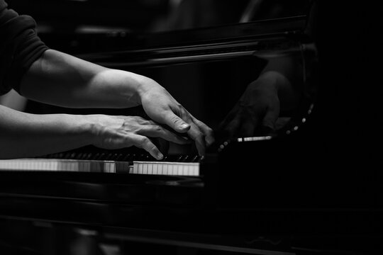 Hands of a woman playing the piano close up in black and white