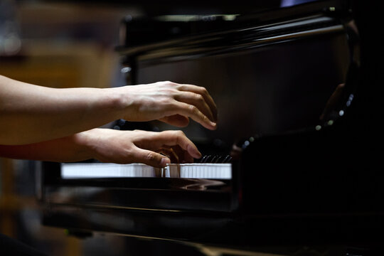 Hands of a woman playing the piano close up