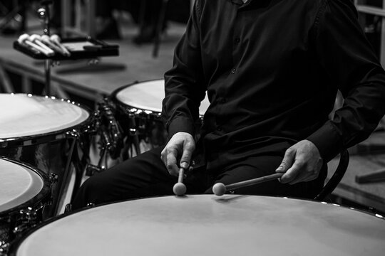 Hands of a musician playing the timpani in black and white