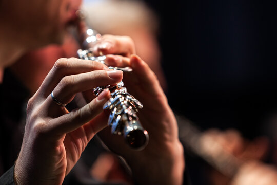 Hands of a musician playing the flute close up