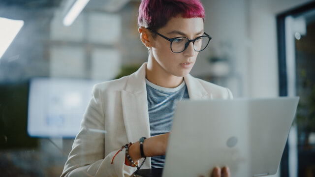 Modern Office: Portrait of Beautiful Creative Specialist with Short Pink Hair Standing, Holding Laptop Computer. Working on App Design, Data Analysis, Plan Strategy for Social Media Disruption