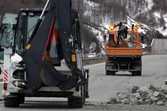 Workers clean the aftermath of a stone landslide at the eighth kilometer of Struma Motorway.