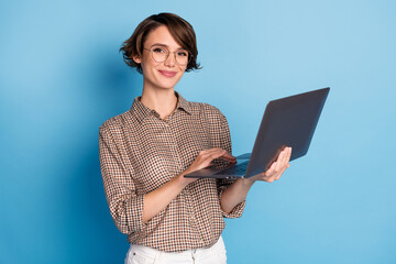 Photo of charming young person hands hold use laptop smile look camera isolated on blue color background Wall mural