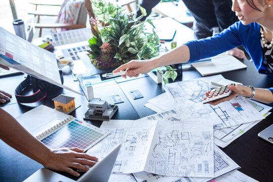 机に広げた資料で会議するデザイナー達