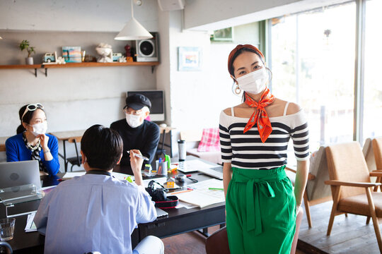 マスクをしたデザイン事務所で働くスタイリッシュな女性