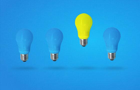 yellow light bulb among blue light bulbs