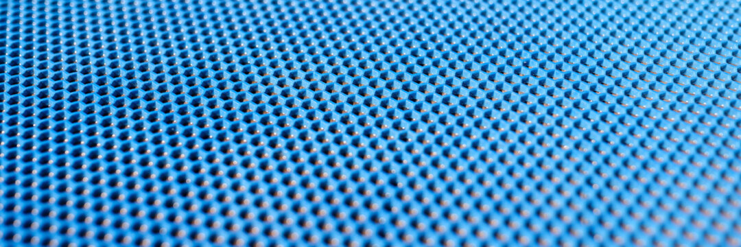 Blue plastic background with holes. Manufacture of plastic products with various textures and patterns.