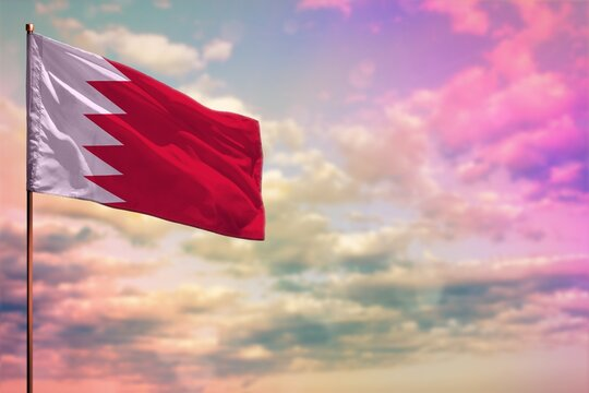 Fluttering Bahrain flag mockup with the space for your content on colorful cloudy sky background.