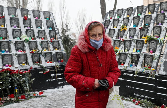 A woman visits a monument to the people killed during the Ukrainian pro-European Union protests in Kyiv