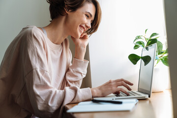 Happy beautiful girl smiling while working with laptop at window