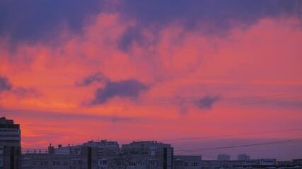 Fotobehang - Beautiful blue clouds in pink sunset sky, dusk city skyline silhouette in background. Timelapse, 4K UHD.