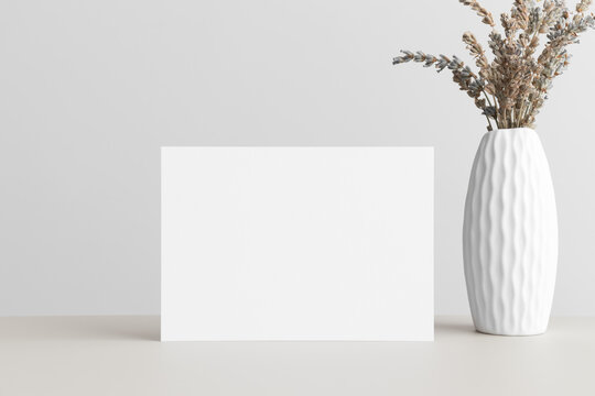 White invitation card mockup with a dried lavender on a beige table. 5x7 ratio, similar to A6, A5.