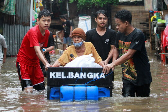 Youths transport an elderly woman using a makeshift raft in an area affected by floods following heavy rains in Jakarta