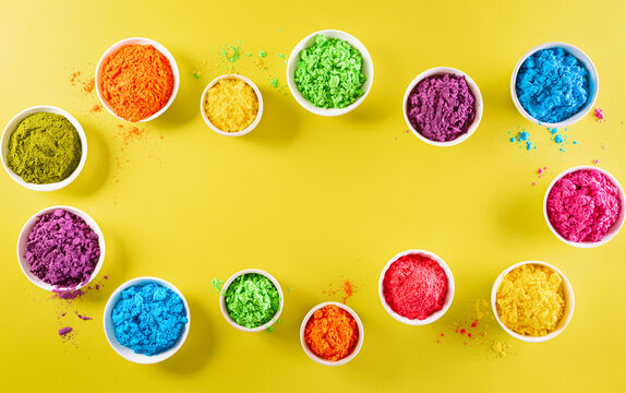 Happy holi festival decoration.Top view of colorful holi powder on yellow  background with copy space for text.