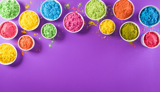 Happy holi festival decoration.Top view of colorful holi powder on purple  background with copy space for text.