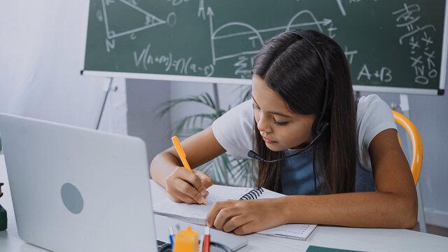 schoolkid in headset writing in notebook near laptop on desk