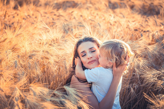 Little beautiful child is hugging his mom in a wheat field