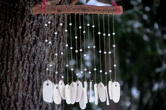 Hand made wind chimes hanging on a string with depth of field effect. Ceramic wind chime hanging outside, selective focus, Wind bells from clay