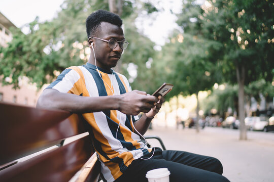 Millennial hipster guy in spectacles searching audio content for download on smartphone technology using 4g wireless internet connection in city, male blogger in earphones listening music playlist