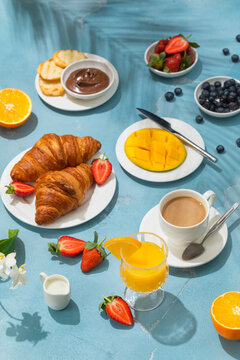 Luxury sunny continental breakfast on blue concrete background table with tropical plants shadows