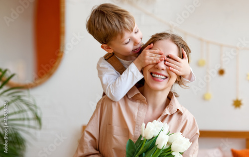 tender son closes his mother's eyes, making her a surprise and gives her a bouquet of tulips, congratulating her on mother's day