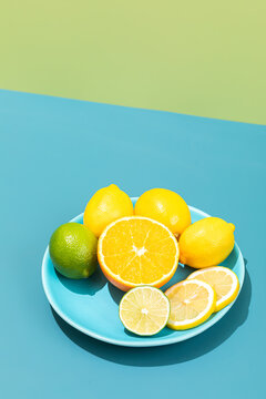 Lemons and limes on the plate isolated on a bright blue and green background, hard light