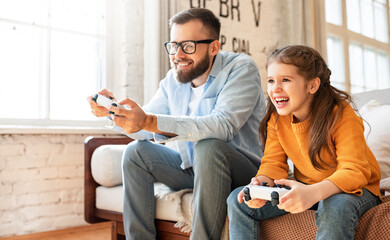 Fototapeta father and daughter laugh and play video games together using a video game console obraz