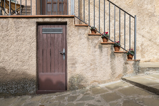 Basement door and vintage stone house entry stairs decorated with flower pots