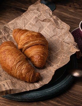 Freshly baked croissants on the old paper rustic background