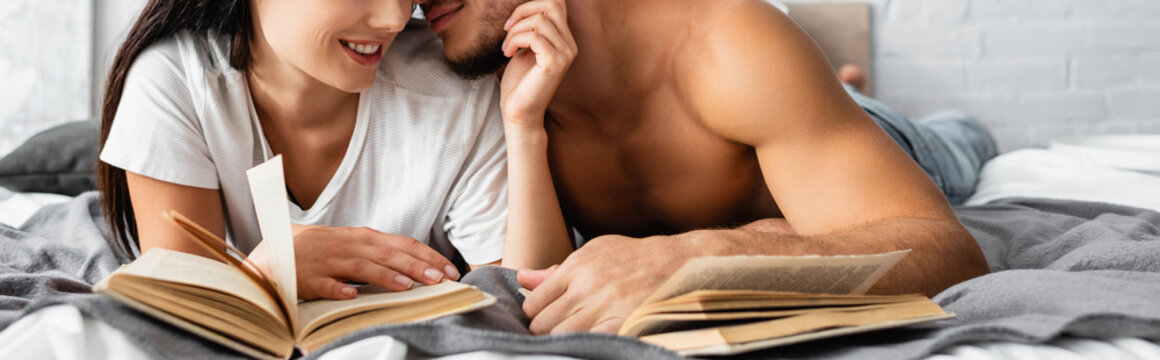 Cropped view of sexy man kissing smiling woman with book on blurred foreground on bed, banner