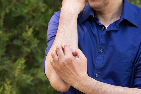 Close-up of man scratching arm because it stings in a park with a green background
