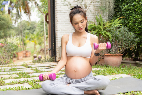 Beautiful pregnant woman doing sport with dumbbell in summer park.