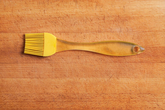 A yellow kitchen silicone brush sits on the cutting board