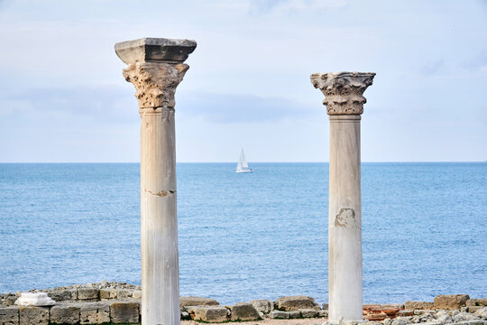 two dilapidated antique columns against the background of the sea, where you can see a blurred sailing ship