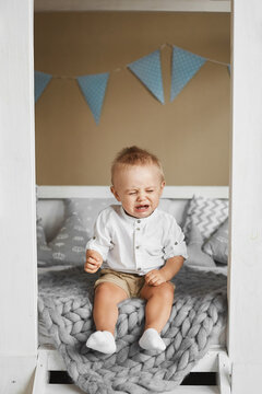 Little boy crying while sitting on the bed