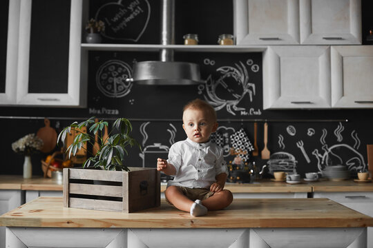 Toddler boy in a white shirt and shorts looking aside while sitting on the kitchen table