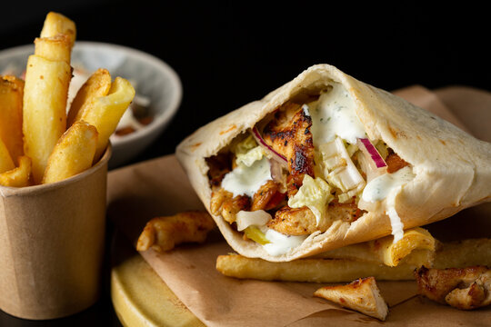 Close up of chicken and vegetables pita and potato fries
