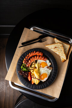 Overhead view of breakfast with eggs on black plate on black table
