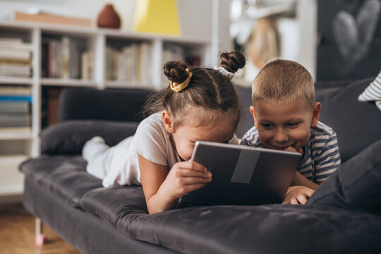 children are playing together at home. They are using digital tablet while laying on a sofa.