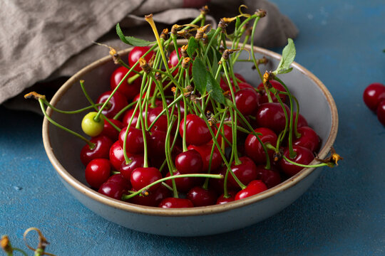 Fresh sour cherries in bowl close up, summer fruits