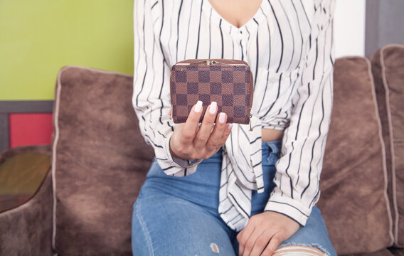 Young woman holding brown wallet at home.