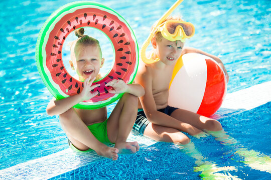 Little cute children near the swimming pool. Kids having fun at summer.