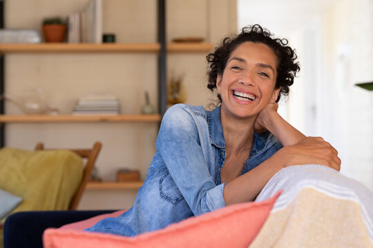 Portrait of caucasian woman sitting on sofa and smiling to camera, relaxing at home