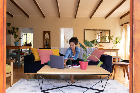 Caucasian woman using laptop, sitting on sofa at home