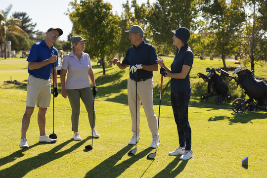Four caucasian senior men and women holding golf clubs and talking