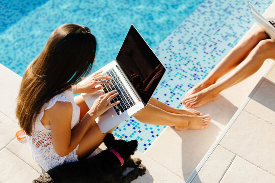 woman using laptop and smartphone on beach pool. Woman freelancer working on laptop on edge of pool. Female study online easily. Using multiple devices.
