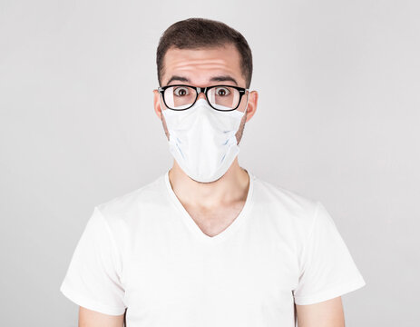 A surgeon in a white medical mask and glasses stands with surprise on a white background. after contracting COVID 19, flu and seasonal colds.