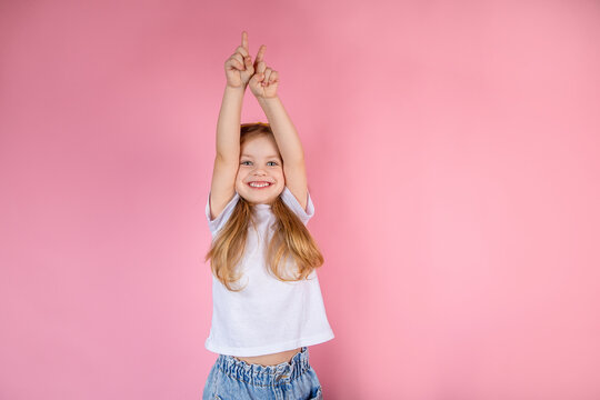 Little girl stretches her arms up while standing on a pink background