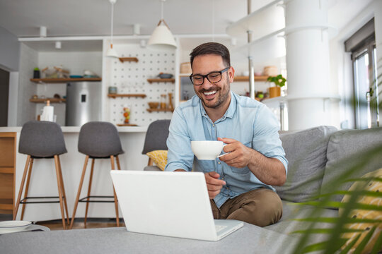 Man  rest on sofa put notebook on lap looking at screen watching movie enjoy lazy free day, creates blog, booking on-line, buyer choose goods makes order, shopping in internet lifestyle concept